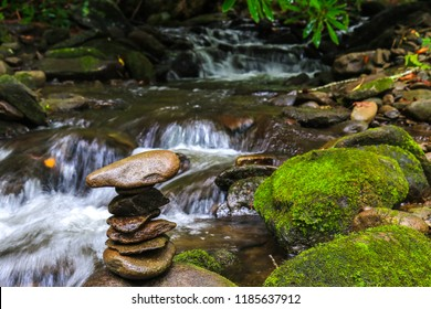 Stacked spa rocks with cascading water over mosey rocks in creek in background; nature meditation concept