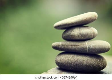 Stacked spa stones with a nature green background.
