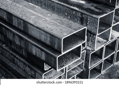 Stacked steel pipes with rectangular cross-section, close-up monochrome photo with selective focus