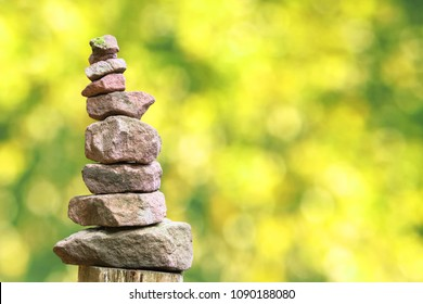 Stacked stone pyramid in front of green blurry background with bokeh