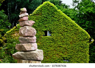 Stacked stone pyramid from sandstone in front of an eco house