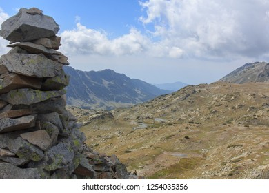 Stacked stones on hill side in Pirin mountains. Left by some hiker, overviewing a valley, with some small lakes, rocks and grass. around 2000 meter height level. Pirin Mountains, Bulgaria
