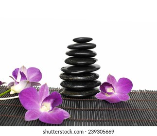 Stacked of stones and orchid on bamboo mat