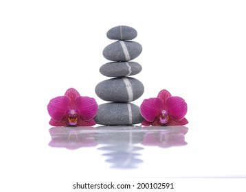Stacked of striped stones and two orchid reflection