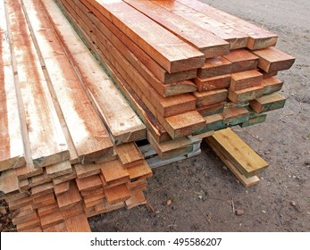 Stacked timber wood boards planks squared impregnated with preservative liquid.