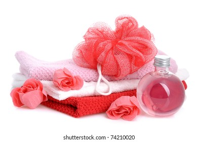 stacked towels with red soap roses and  red bath sponge on white background