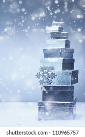 A stacked tower of silver Christmas gifts in diminishing sizes and different angles in falling snow with copyspace
