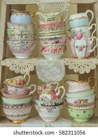 Stacked vintage milk jugs and sugar bowls on a rustic ladder shelf with lace doilies