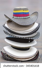 Stacked white and colored Colombian tourist hats laying on the floor of a square in Medellin. Colombia (Selective focus)