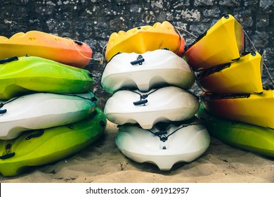 Stacked white, green and orange kayaks on a beach