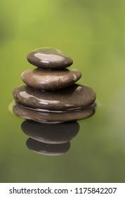 Stacked zen boulders reflected in green water