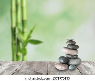 Stacked zen stones on wooden table in garden, space for text
