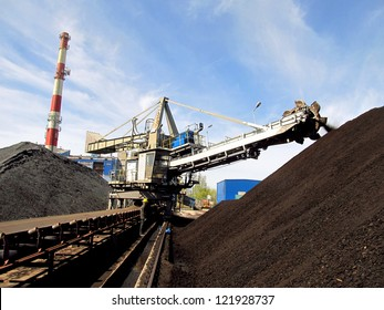 Stacker with a heap of coal next to the plant