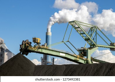 Stacker-reclaimer in a coal handling terminal with in the background a brown coal power plant.
