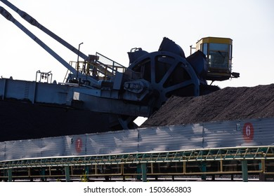 Stacker-reclaimer during loading and unloading of coal. Coal heaps at a marine coal terminal