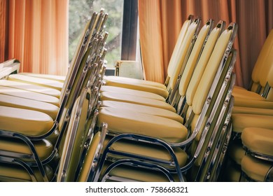 Stacking Banquet Chairs with Seat Cushion. Metal Structured Cream Color Chairs organized in Piles in the Ceremony Hall or Ballroom