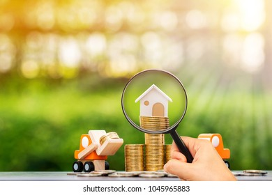 Stacking coin growing and home on the top and a hand hold a magnifying glass searching for a new home in the public park, Loan for real estate or save money for buy a house to in the future concept.