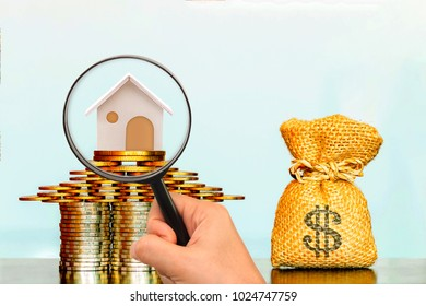 Stacking coin growing and a money bag and a hand hold a magnifier searching for a new home on blue background, Loans for real estate or save money for buy a new house to family in the future concept.