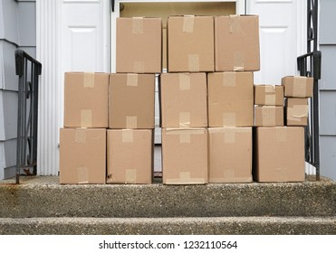 stacking delivered package boxes in front of the front door of house
