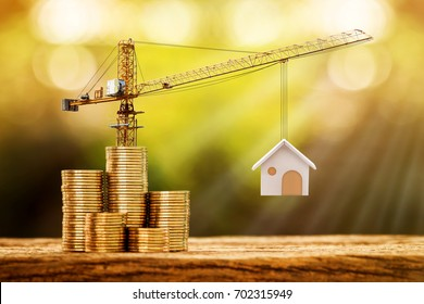 Stacking gold coins with increase and tower crane and hoist brake solutions with build new house in the public park, saving money and loan for construction real estate and home concept.