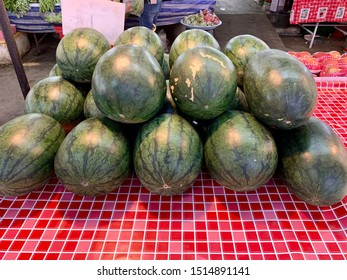 Stacking watermelons for sale in the market.