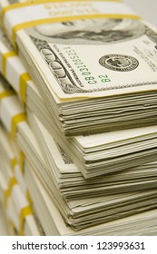Stacks of $100 bills banded in $10,000 amounts with a yellow band
