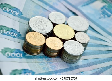 stacks of all kinds of russian coins on the one thousand rubles banknotes background. russian money for illustrations and backgrounds