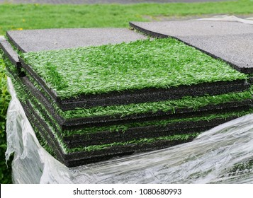 Stacks of artificial turf grass rug tiles with rubber under layer for indoor, outdoor landscaping