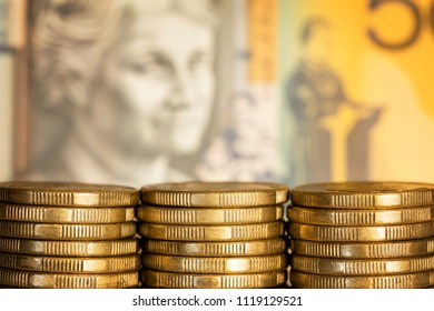 Stacks of Australian dollar coins over blurred money background.