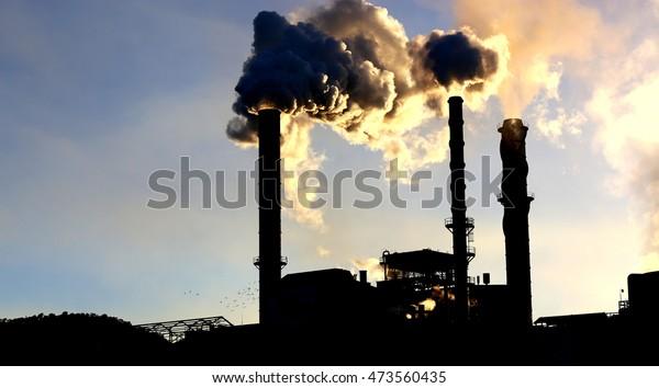 Stacks billowing smoke into blue skies.Industrial mine sites .Mine stacks or sugar cane mills and steam stacks. Smokestacks