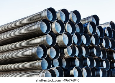 stacks of black pvc plastic pipe outdoors outside the warehouse