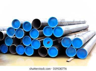 Stacks of black water pipes isolated on white background