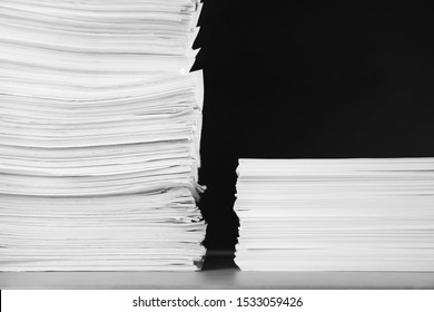 Stacks of blank paper on grey stone table against black background