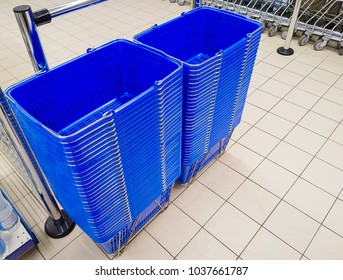 Stacks of blue plastic shopping baskets in a supermarket. Selective focus.