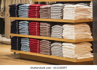 Stacks of clothes arranged on measure sizes in a store.