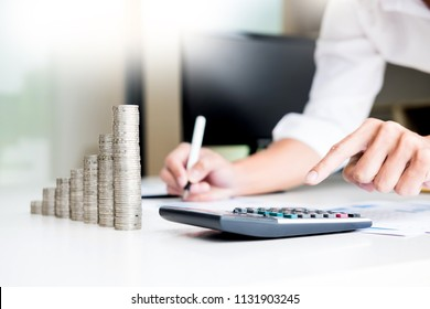 stacks of coins business accounting with saving money  concept calculator counting, making notes at home, hand is writes in a notebook. Stacked coins arranged, graph, chart and pen.