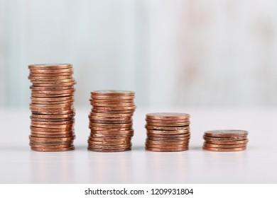 Stacks of coins in a decrease financial concept.