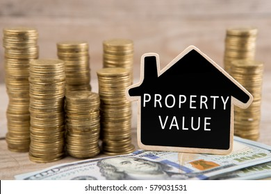 "Stacks of coins and dollar bills, blackboard in the shape of a house with text ""PROPERTY VALUE"" on wooden background. Business and Financial concept"