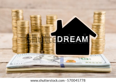 Stacks Of Coins And Dollar Bills Blackboard In The Shape Of A House With Text
