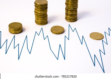 Stacks of coins near graphics with rise and fall - where high performance - high stack, where fall - is low. Financial performance or level of company profits, stock market, market cryptocurrency
