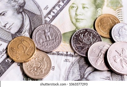 Stacks of coins with a variety of countries both in Asia and Europe on banknotes background. such as British one pound, euro coin, baht of Thailand, Hong Kong dollar, Chinese coin.