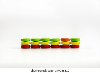Stacks of colorful candy with a broken pattern on a white background. Could be used for abstract concepts of being different or individuality.  Room for copy space.
