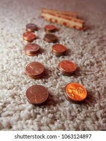 Stacks of copper American pennies are lined up on a carpet in preparation to be packed into paper rolls of 50.