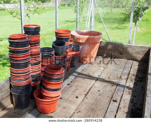 Stacks of dirty plastic flowerpots on a wooden bench in a greenhouse - horizontal
