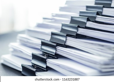 Stacks documents files with black clip.