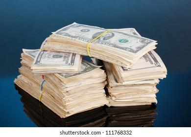 Stacks of dollars on blue background