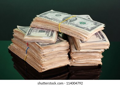 Stacks of dollars on green background