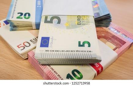 Stacks of Euro bank notes in 5s, 10s, 20s and 50s on a light pine desk