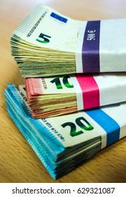 Stacks of Euro bills of fives, tens and twenties on a pine desk.