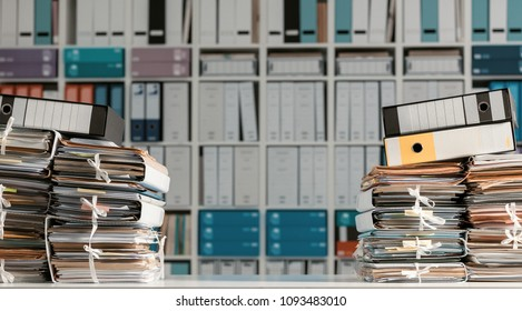 Stacks of files and paperwork in the office and bookshelves on the background: management and archive concept